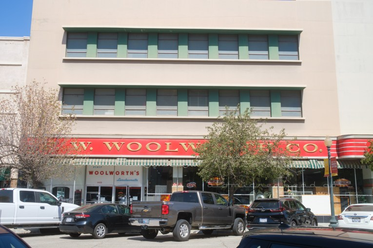 """The side of the Woolworth's with the long """"F.W. Woolworth's"""" sign stretching the ling of the photo."""