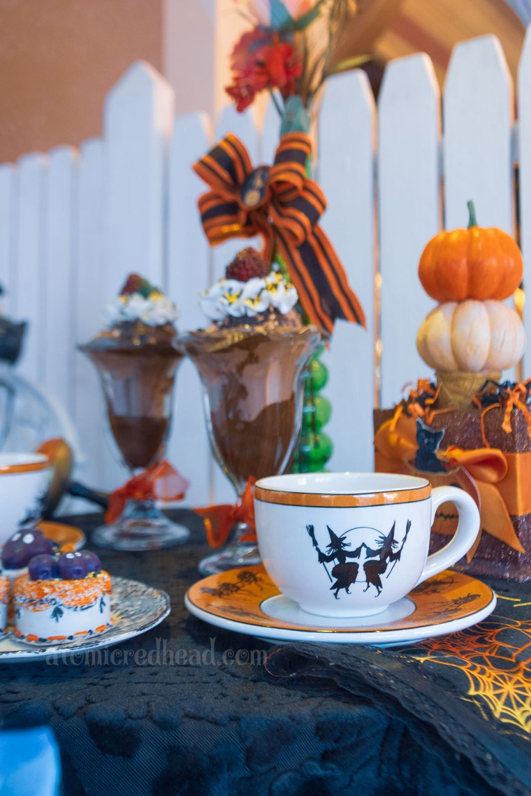 A small table and chair sit in the window of the ice cream parlor. On the table are two sundaes, and a cup and saucer, featuring two dancing witches.