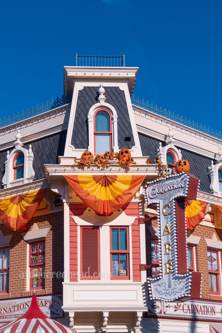 """Exterior shot of the upper level of the Carnation Cafe, a red and white building in the late 1800s, early 1900s style. Bunting of red, orange, and yellow hangs from eves, and several Jack O'lanterns sit on edges. A sign juts out from the building on the left reading """"Carnation Cafe"""""""