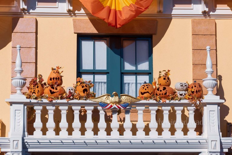 A small white balcony is home to several carved Jack O'lanterns with funny facies.