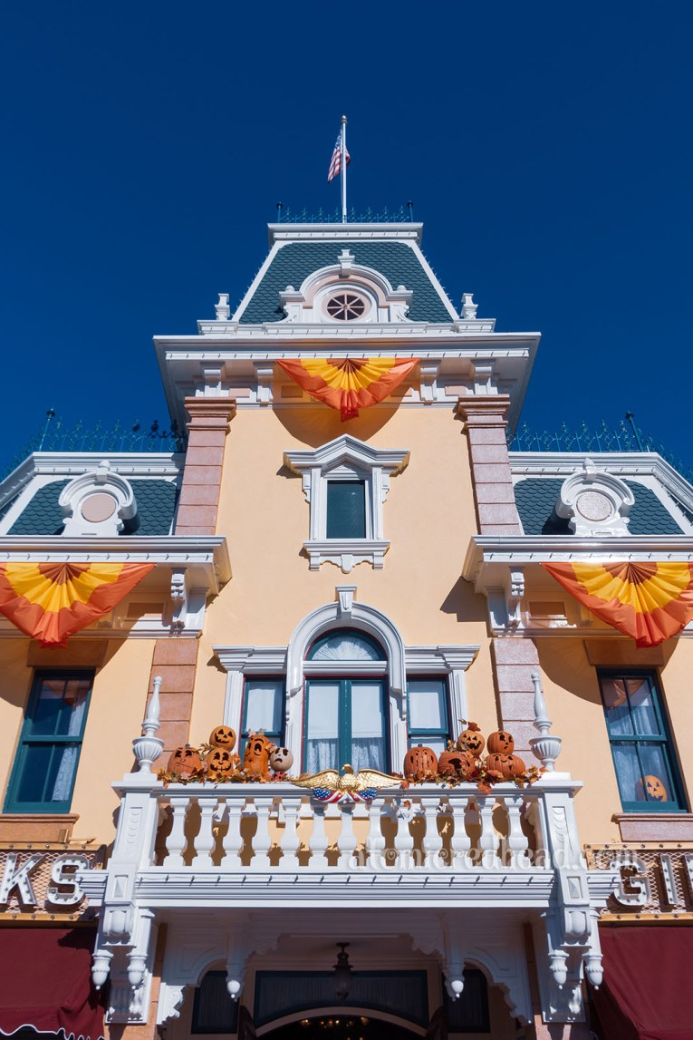 Exterior shot of the Disneyland Emporium. Painted a light beige color, with blue roof and white details, bunting of red, orange, and yellow hangs, and carved Jack O'lanterns sit on a blacony.