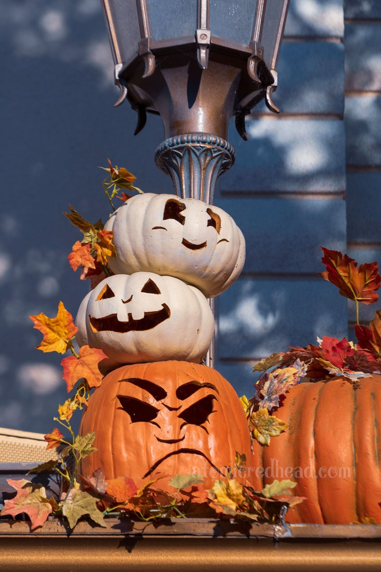 Two small happy faced white Jack O'Lanterns sit atop an orange, grumpy faced one.