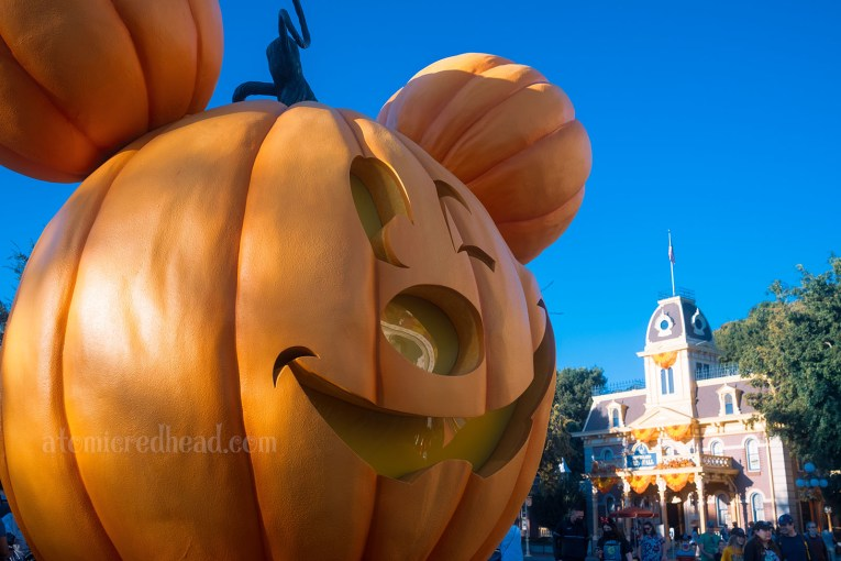 A massive Jack O'lantern sits in the middle of Main Street and features a carved face of Micky Mouse winking.