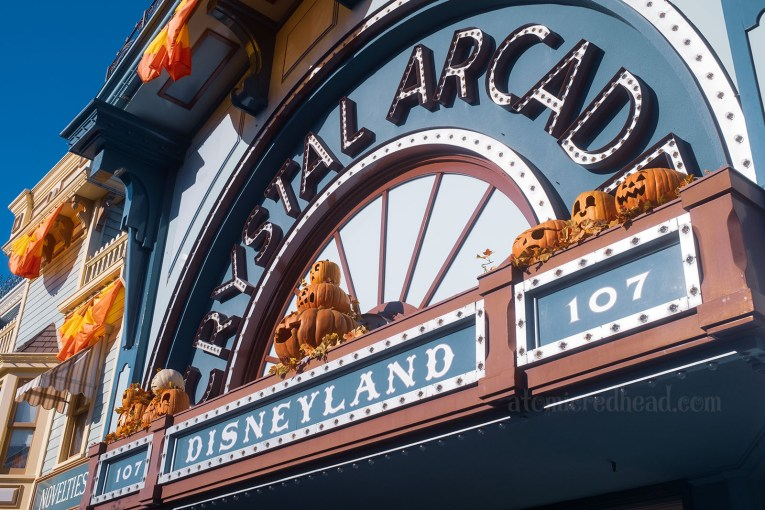 """Front of the Crystal Arcade. A teal and red building with bulb letters spelling out """"Crystal Arcade"""" and a smaller sign below reading """"Disneyland"""""""