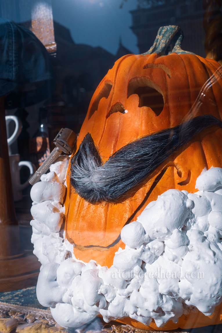 A pumpkin appears to be shaving inside a Main Street window, with a mustache and lathered soap and razer.