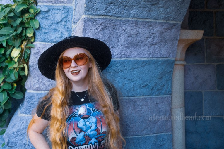 """Myself, wearing a black straw hat, black tee featuring Goliath, a massive gargoyle, and gothic script reading """"Gargoyles"""" standing in front of the stone walls of Sleeping Beauty Castle."""