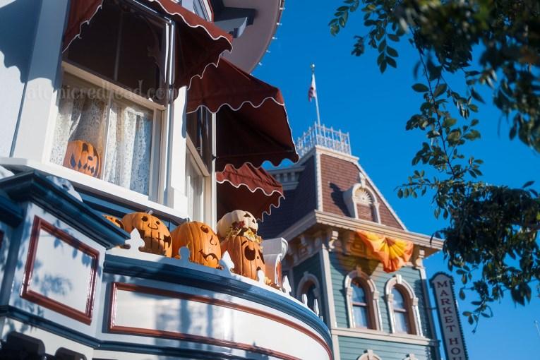 Various Jack O'lanterns sit atop ledges of Main Street buildings.