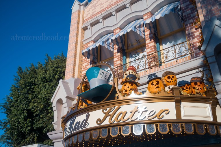 An awning for the Mad Hatter Shop features various Jack O'lanterns, each wearing hats.
