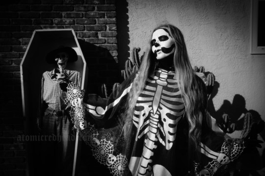 Myself, with a full black and white skull face paint, a skeleton lace poncho, standing in front of a coffin with a skeleton in it.