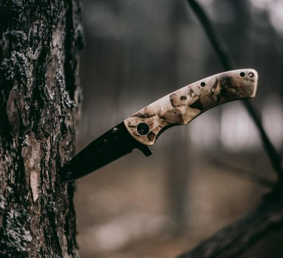 fixed blade knife with camouflage handle stuck sideways into tree