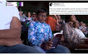 Kid reading book in Federer-Nadal Match
