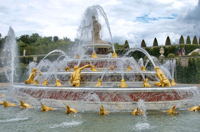 Gold fountain with four layers, with water spouting upwards from frogs and humans