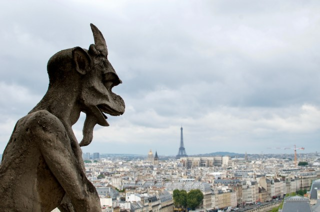 Grotesque looks out over the city of Paris, including the Eiffel Tower, from the top of Notre Dame