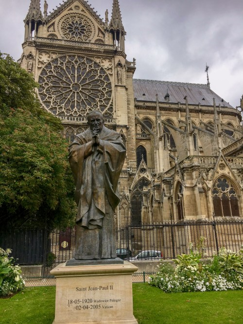 Statue of Pope Jean Paul II outside of the facade of Notre Dame, before the fire in 2019