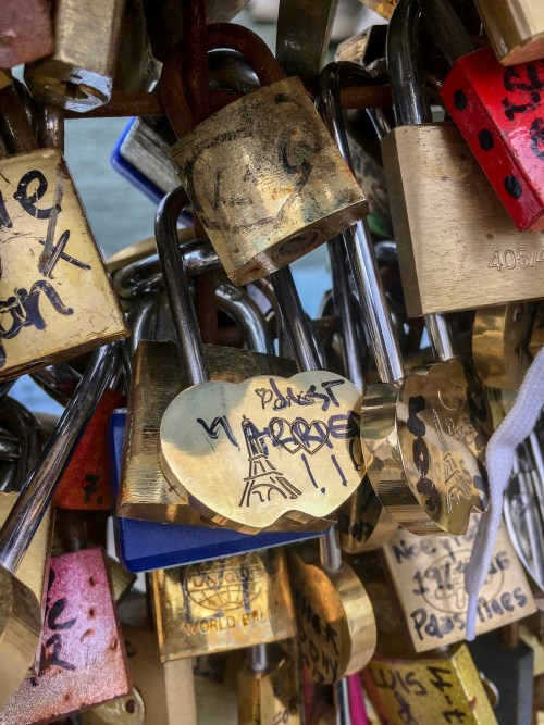 "Locks of all kinds strung together, one of them in the middle has a picture of the Eiffel Tower and reads ""Just Married"""
