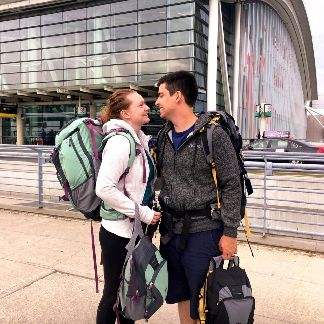 Man and woman facing each other, with backpacks on their backs and smaller ones in their hand, standing outside of an airport