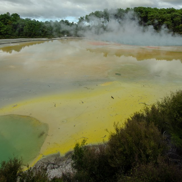 Geothermal area, covered in green, yellow and orange, with mist rising from the mat