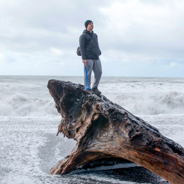 Man in black coat and hat standing on piece of driftwood twice his size, at edge of ocean wave break