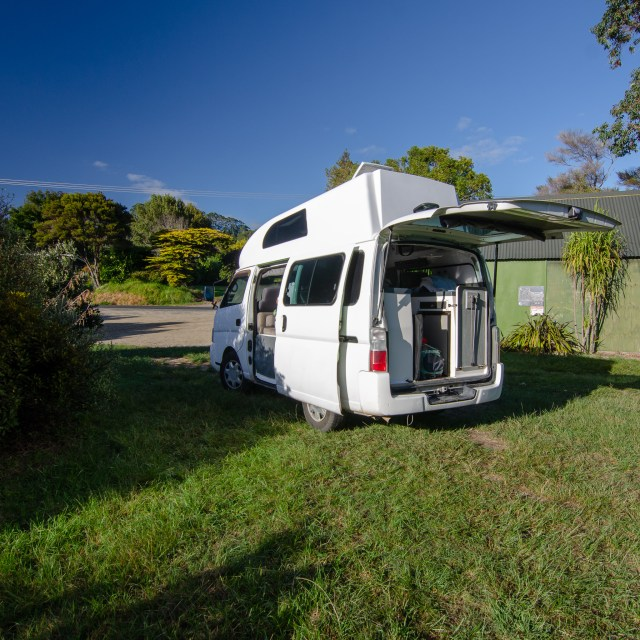 Campervan with back open, in a grassy field