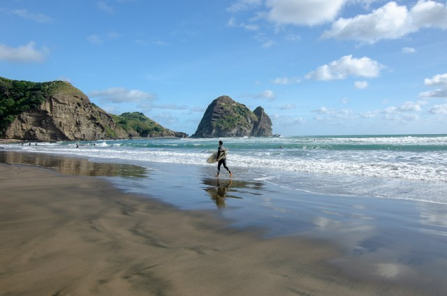 Surfer with surfboard walks across a reflective beach, with blue water and sea stacks in the background