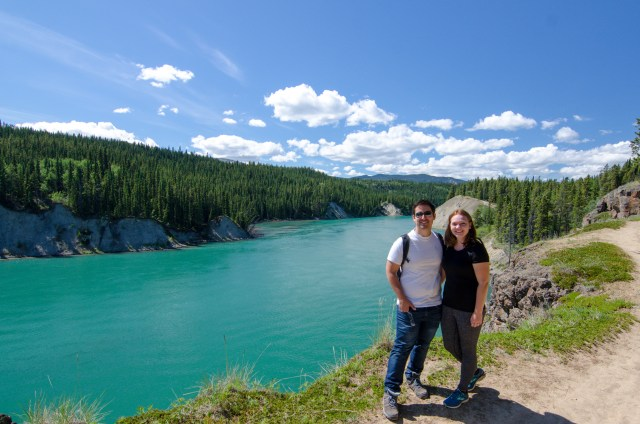 Man and woman standing in front of a turquoise river running through a canyon