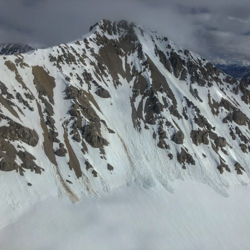 Aerial view of snow covered mountains, with avalanches down the sides