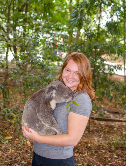 Woman with red hair holding a koala and smiling at the camera, amongst a backdrop of eucalyptus forest
