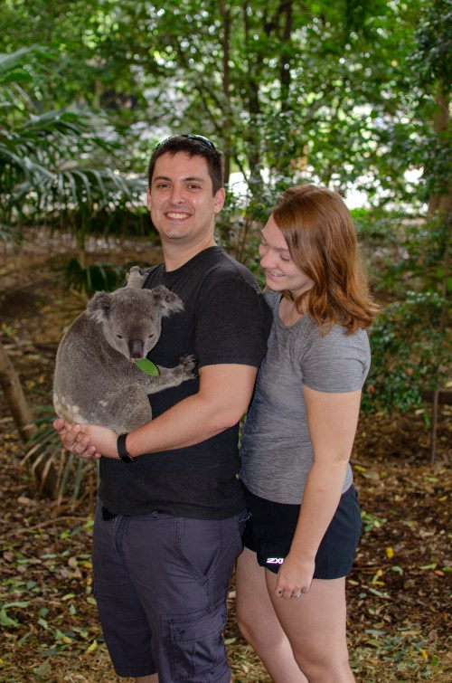 Man smiling at camera, holding a koala, and woman standing directly beside him looking at the koala