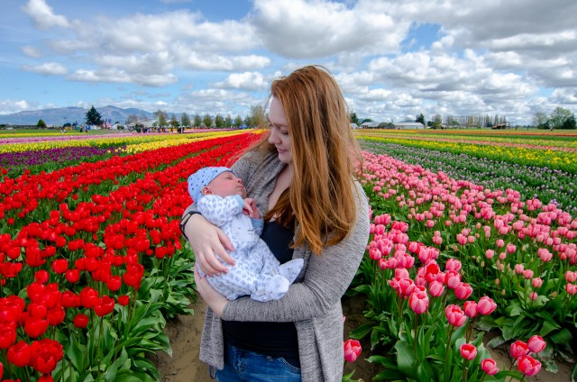 Woman with red hair holding baby, amongst colorful tulip fields