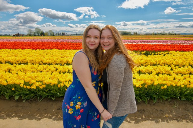 Two women, one with red hair and one with blonde, holding hands and smiling in front of tulips