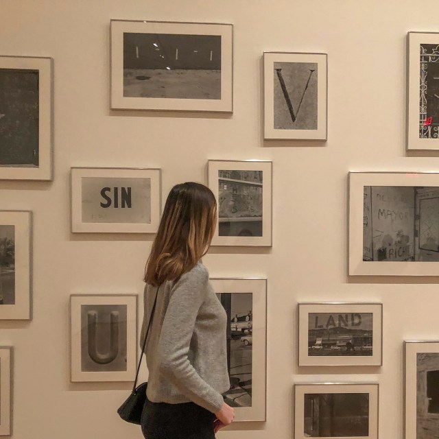 Woman looking at black and white photos in frames at Museum of Modern Art