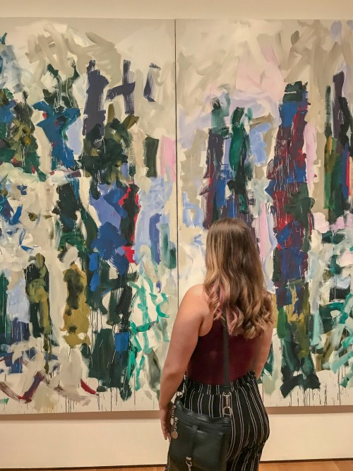 Woman facing towards a modern painting, that includes overlapping colors in lines. She has her feet cropped out of the photo