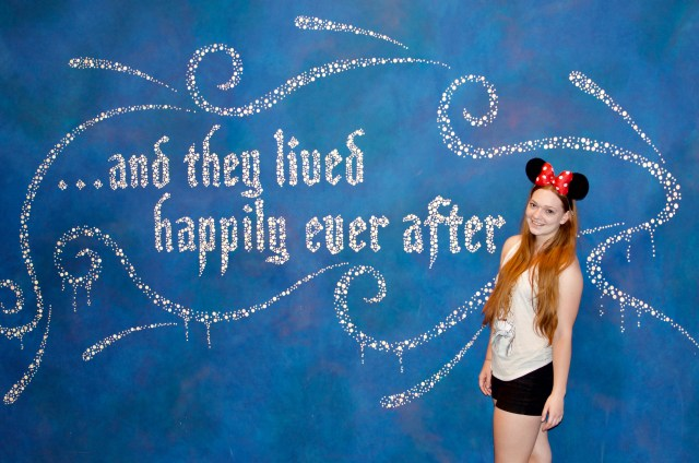 "Woman in red Minnie ears standing in front of blue wall reading ""and they lived happily ever after"" in silver cursive lettering"