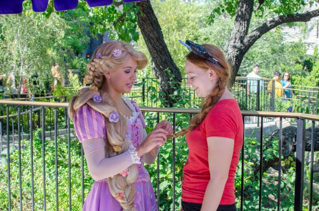 Costumed Rapunzel playing with the long braid of girl dressed in red with blue Disney ears