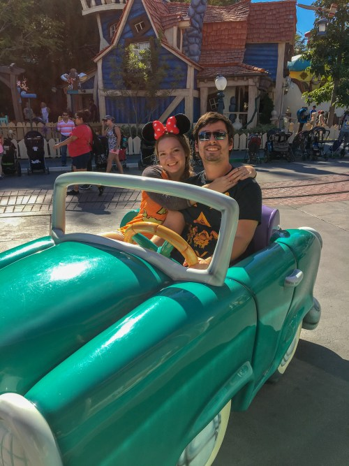 Woman and man in Halloween shirts sitting in green car in Disneyland Toon Town