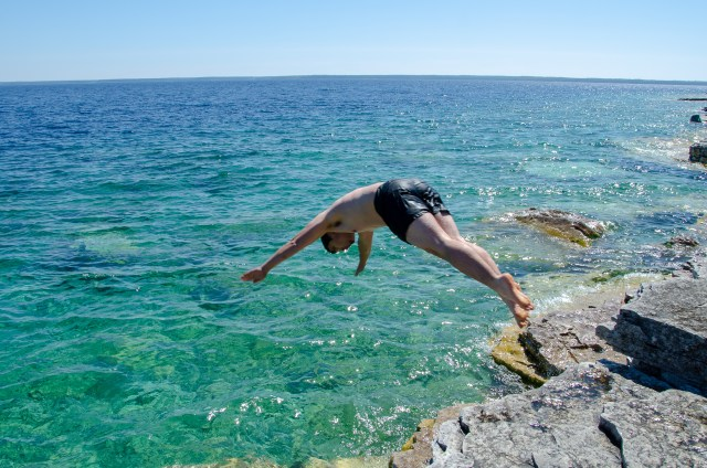 Man in black swim shorts diving into blue, clear water