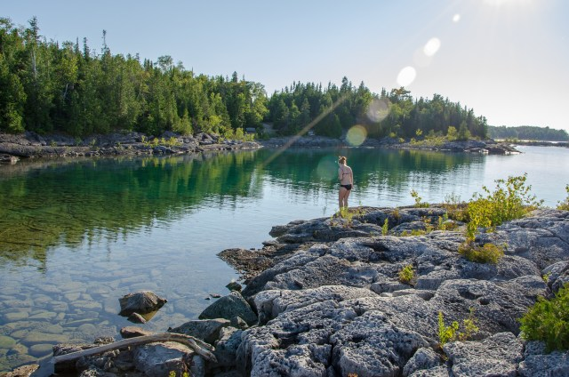 Woman entering greenish blue clear water from rocky island, located in one of the quietest Tobermory attractions