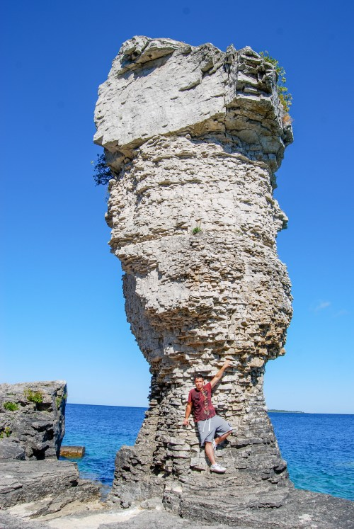 Man standing in front of Flowerpot rock formation, one of Tobermory attractions