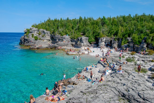 Many people along rocky edge of tree-filled shoreline on the beautiful blue waters of Georgian Bay