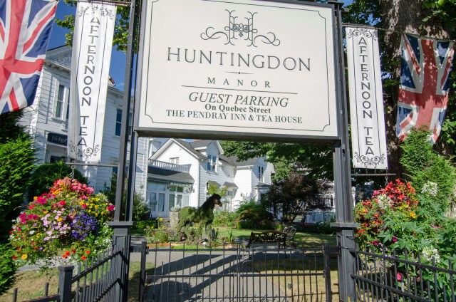 Sign for Huntingdon Manor, with white house in the background, and flowers and British flag in the foreground
