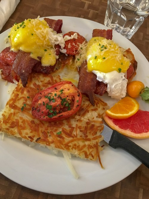 Eggs benedict, hashbrowns topped with a tomato, and assorted fruits