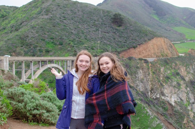 Two girls in front of a bridge that connects two greenery filled cliffs in one of the top places to visit in California: Big Sur