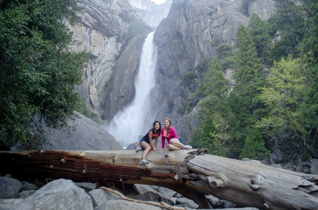 Two females sitting on a massive downed tree, with a tall waterfall in the background