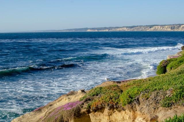 Deep blue water against sand cliffs that have sparse green vegetation
