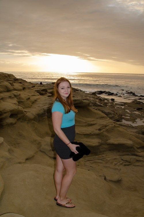 Woman in blue shirt and pencil skirt on bluffs of a beach, with the sun setting in the background