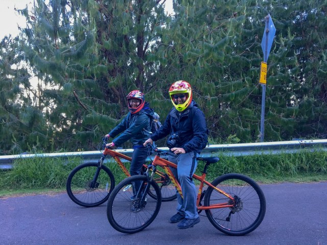 Male and female in windproof jackets and helmets sitting on bicycles