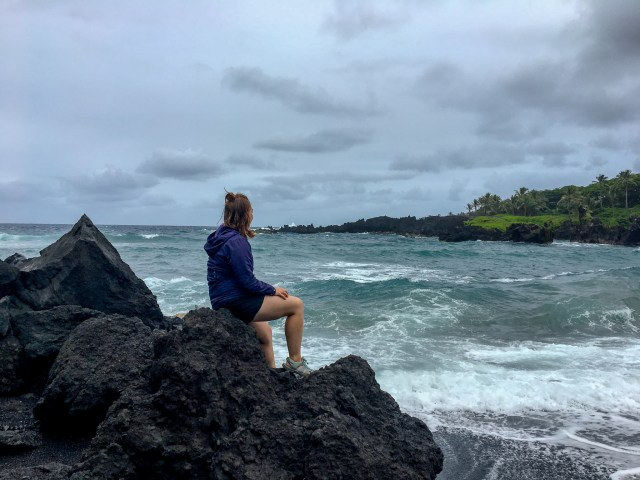 Woman in purple rain jacket sitting on black lava rocks looking out at blue water on black sand beach
