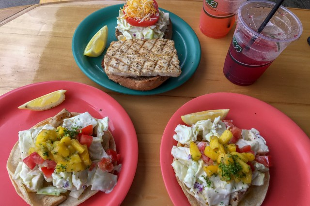 Three plates, two with fish tacos covered in coleslaw and mango, and another with a fish sandwich