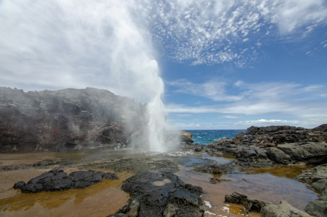 Blow hole coming out of lava rocks, in front of the ocean