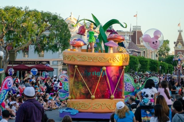 Tinkerbell atop a float in a Disney parade, sprinkling pixie dust with her wand